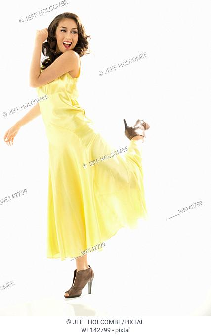 Beautiful young woman dancing in vintage yellow dress, full length in brown heels, one leg kicked back
