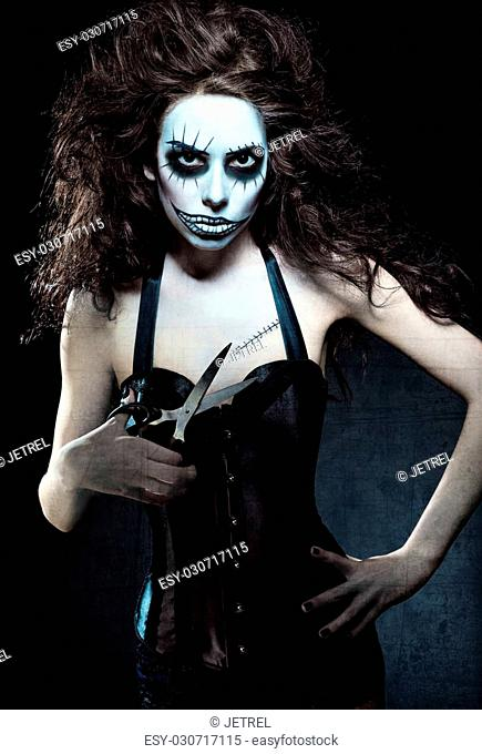 Young woman in the image of a evil gothic freak clown with scissors in hand. Grunge texture effect