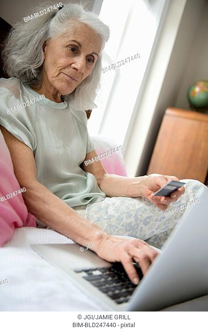 Older woman shopping online with credit card and laptop