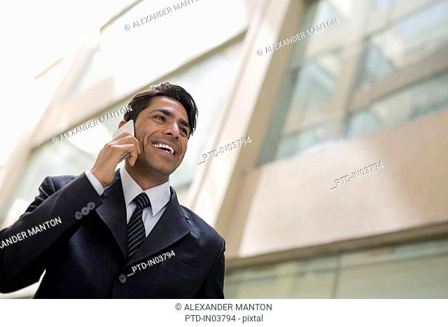 India, Smiling businessman outside office building talking on mobile phone