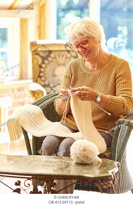 Smiling senior woman knitting scarf