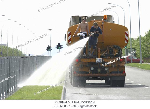 Two men at the back of a water truck, spraying water onto grass beside a street
