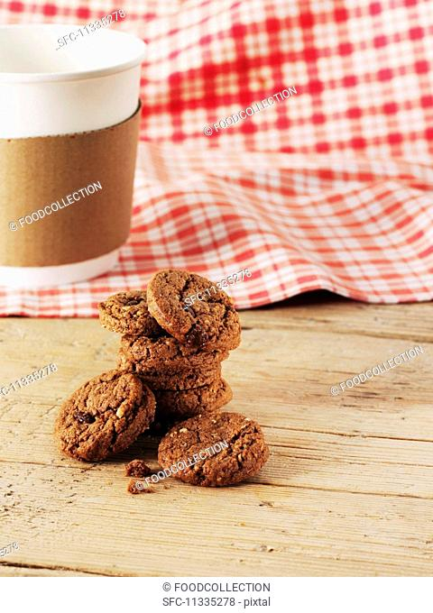 Chocolate chip cookies in front of a coffee cup