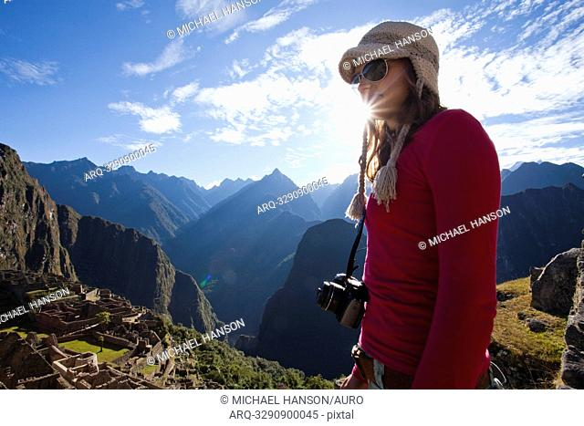 A young girl stands with a camera around her neck overlooking a steep valley, the rising sun, and the ruins of a lost civilization