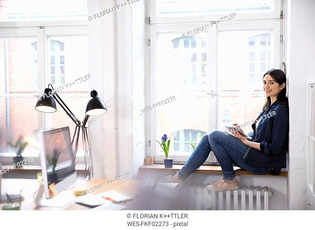 Smiling woman using tablet at the window in office