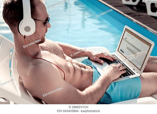 Work is calling. Selective focus on hands and a laptop of a male businessman relaxing on a sunbed and listening to music while working outdoors