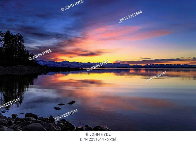 A summer sunset colours the sky adjacent to Lynn Canal, Inside Passage, Chilkat Mountains beyond in the distance; Alaska, United States of America
