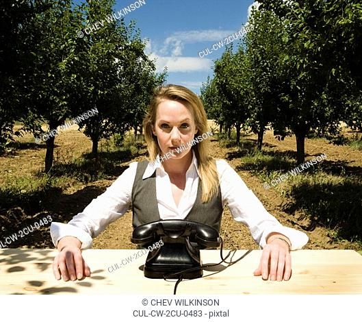 Woman sitting at desk behind old telephone in orchard
