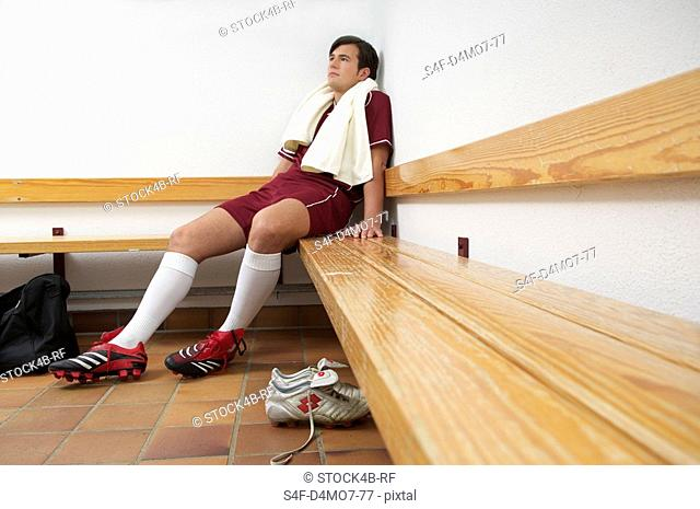 Exhausted kicker sitting in dressing room