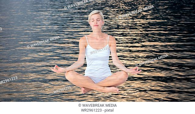 Double exposure of woman meditating over lake