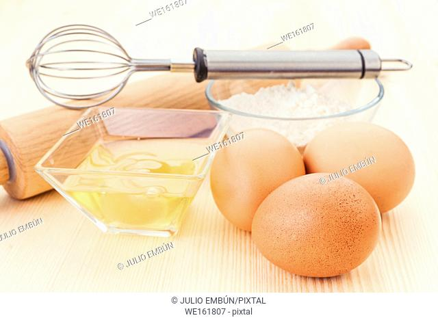 flour eggs and kitchen utensils on natural wood