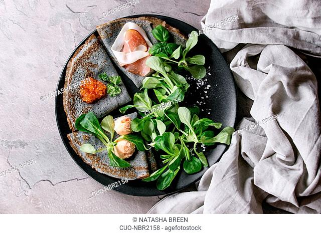 Black pancakes crepes with variety of salt filling red caviar, ham, fish salmon pate, green salad with textile linen napkin over gray texture background