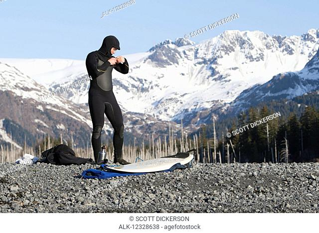 Surfer gearing up to go surfing on the Kenai Peninsula Outer Coast, South-central Alaska; Alaska, United States of America