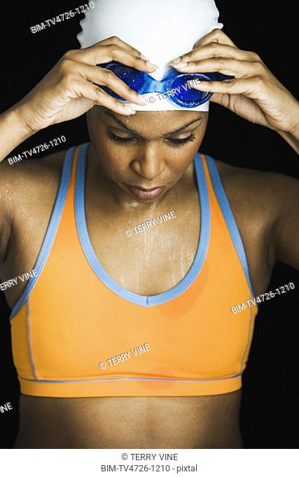 African woman wearing swimming cap and goggles