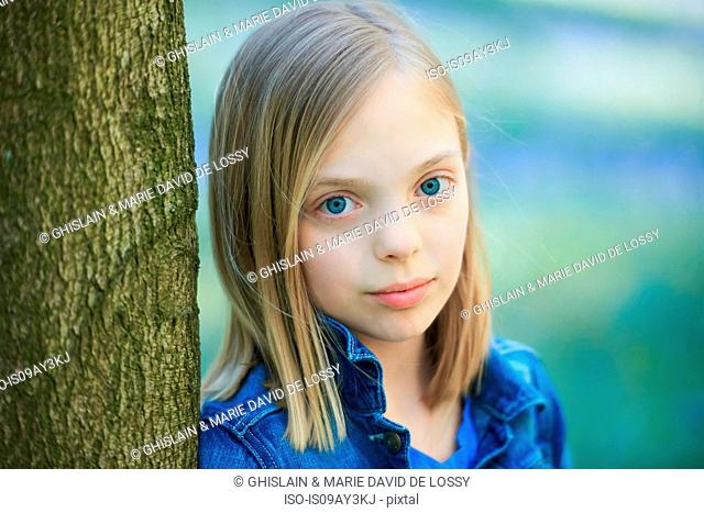 Portrait of blond haired girl leaning against tree in bluebell forest, Hallerbos, Brussels, Belgium