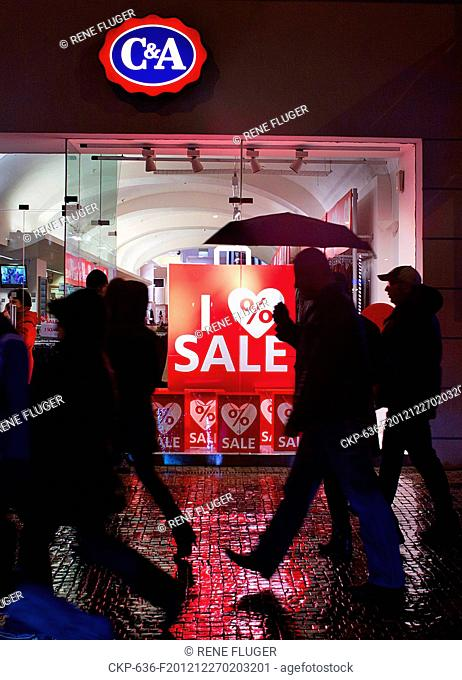 People stroll past sales signs displayed at windows of shopping malls during post Christmas discounts and sales at Wenceslas Square in Prague