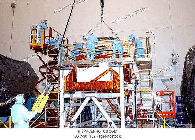12/20/2001 -- In the Vertical Processing Facility, workers watch while an overhead crane lowers the Advanced Camera for Surveys ACS into the Axial Science...