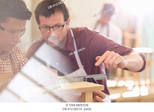 Carpenters measuring wood with ruler in workshop