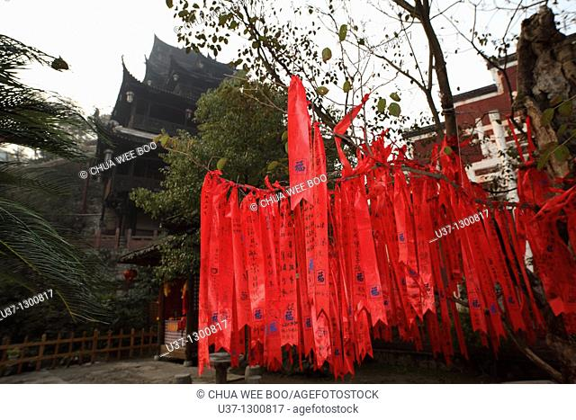 Tujia people make good wishes in red clothes with wordings hanging on trees