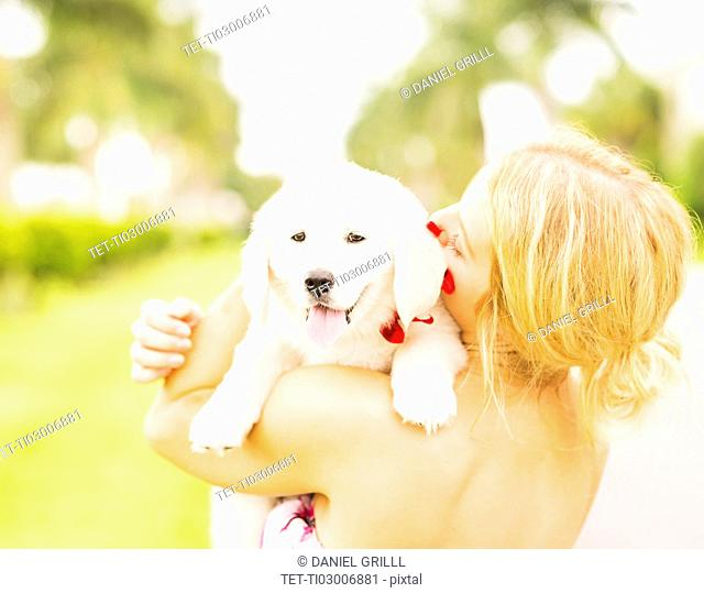 Close-up shot of young woman embracing white puppy
