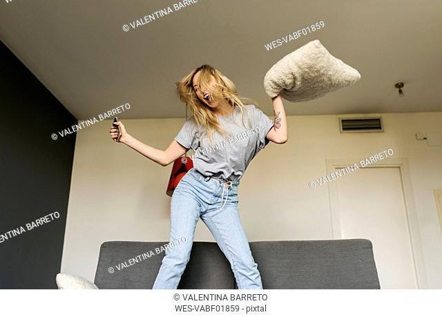 Carefree young woman jumping on couch at home