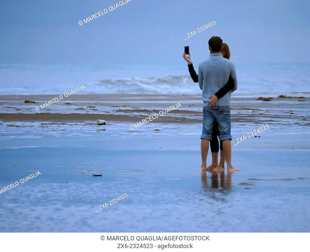 Couple Selfie at Eucaliptus Beach on a stormy afternoon. Ebro River Delta Natural Park, Tarragona province, Catalonia, Spain