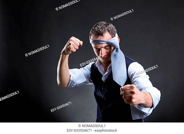 Fighting businessman with a tie on his head in over grey background