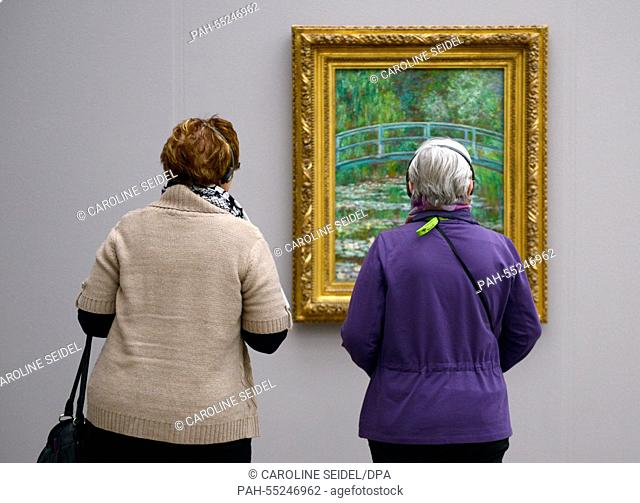 Visitors with audio guides stand before the painting 'The Water Lily Pond' from Claude Monet at the special exhibition 'Monet, Gauguin, van Gogh.
