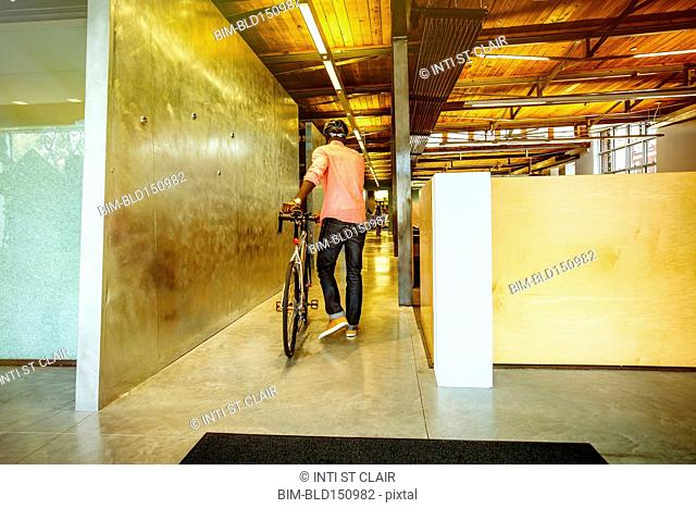 African American businessman pushing bicycle into office