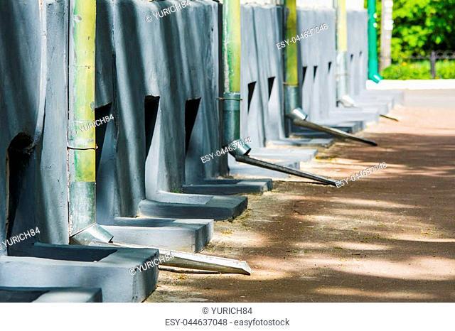 Wall with metal downspouts (rain gutter) go on the sidewalk in sunlight