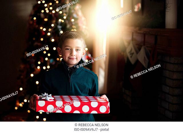 Boy in front of christmas tree holding gift looking at camera smiling