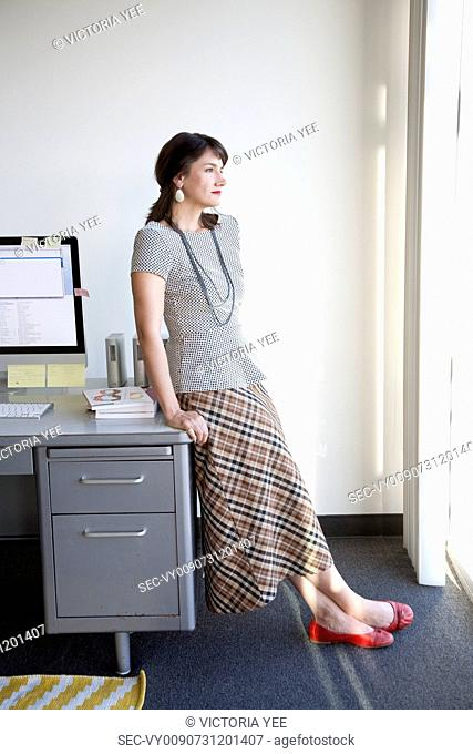 Businesswoman relaxing at her desk in office