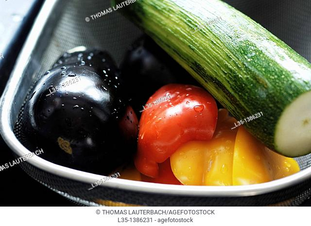 Freshly washed pepper, eggplant and zucchini in a basket