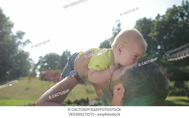 Affectionate young father lifting cute baby boy up