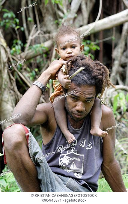 Young melanesian father carrying his daughter on his shoulder, looking into the camera, Tanna island, Vanuatu,  Melanesia, South Pacific