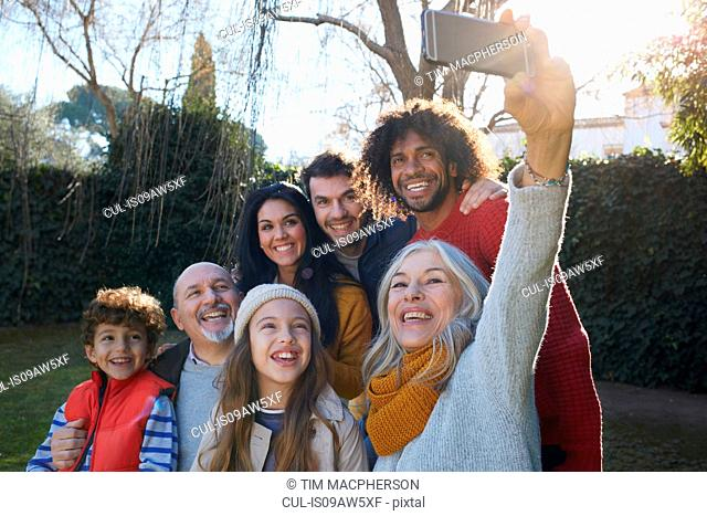 Multi generation family huddled together using smartphone to take selfie, smiling