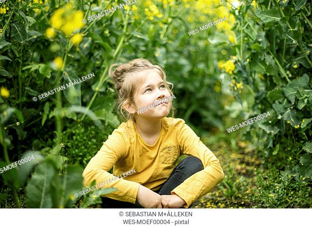 Confident girl sitting in rape field