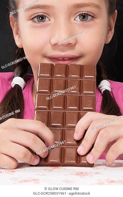 Girl holding a bar of chocolate