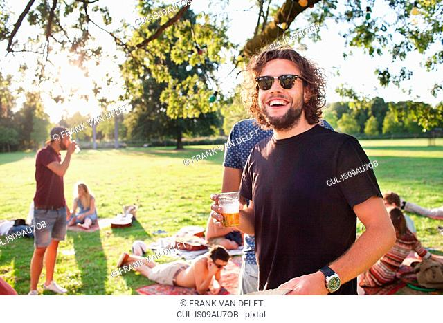 Portrait of young man drinking beer at group party picnic in park