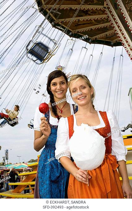 Two women with toffee apple & candy floss by swing rideOktoberfest