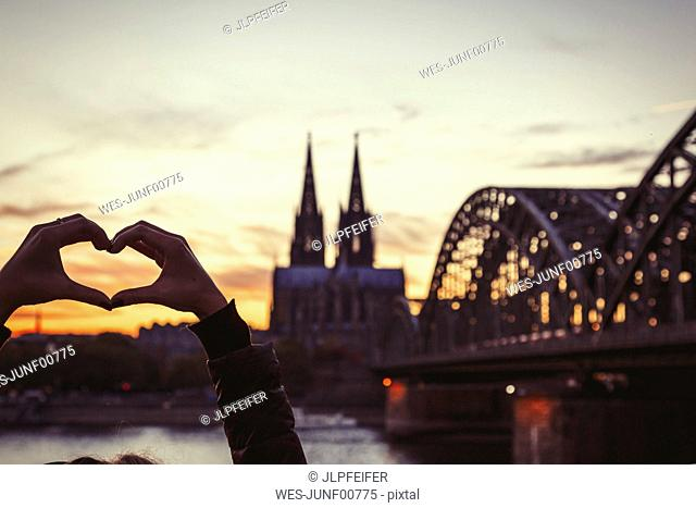 Germany, Cologne, woman shaping heart with her hands in front of Cologne Cathedral and Hohenzollern Bridge at dusk