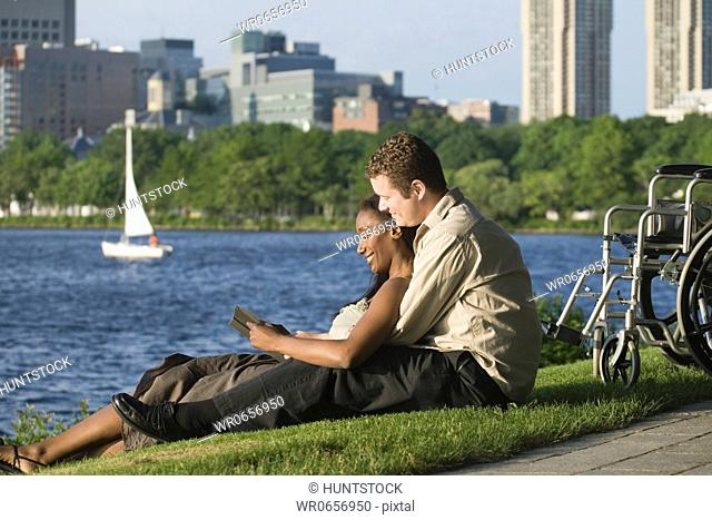 Side profile of a mid adult couple sitting in a park and reading a book, Boston, Massachusetts, USA