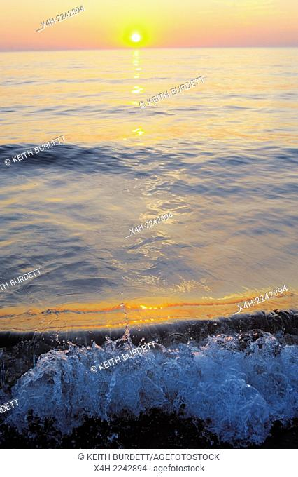 Sun setting into the sea with small breaking waves, Wales, UK