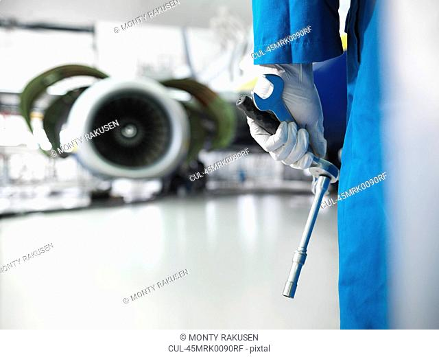 Worker holding tools in airport hangar