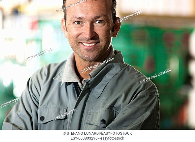 Close-up of a smiling mechanic inside his auto repair shop