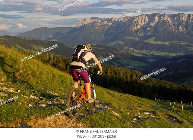 Austria, Tyrol, Spitzstein, Young woman mountainbiking on slope with Kaiser mountains in background