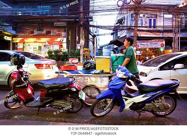 pedestrians and traffic on suburban Bangkok shopping district