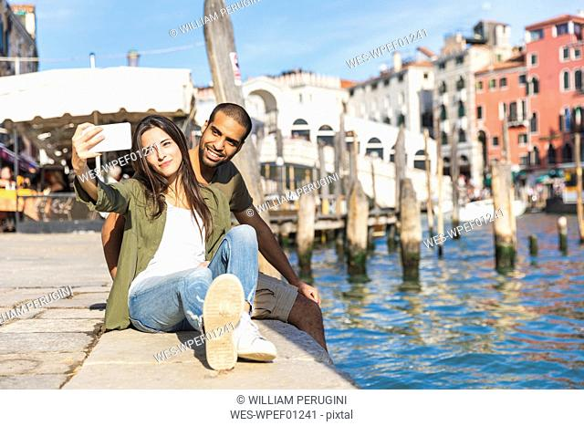 Italy, Venice, couple relaxing and taking a selfie with Rialto bridge in background