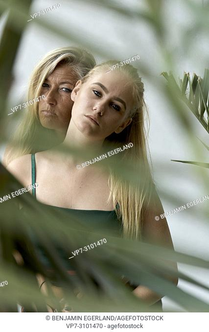 Portrait of mother (43 years) with teenage daughter (13 years) behind leaves, intimate, togetherness. Danish ethnicity