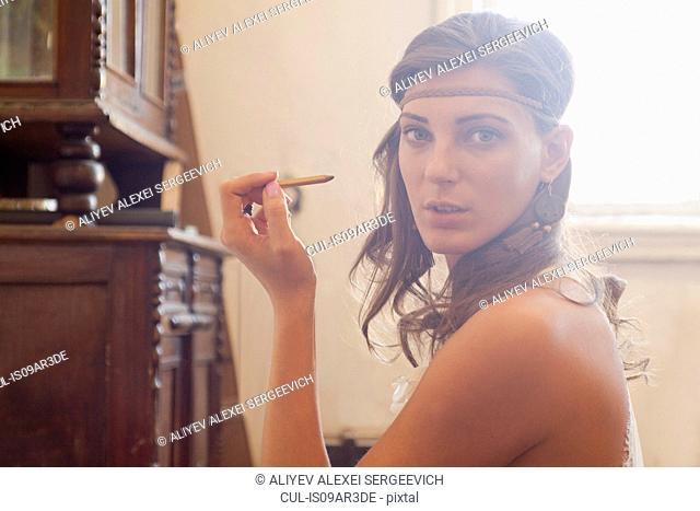 Portrait of young woman, applying eye pencil